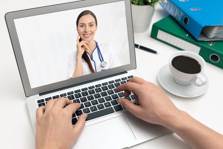 Médico con un estetoscopio en la pantalla del portátil. Concepto de telemedicina o telesalud