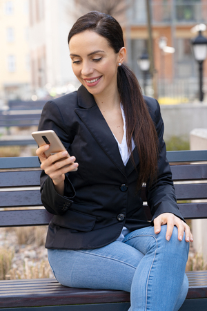 Portrait of attractive business woman sitting on a bench and using her smartphone