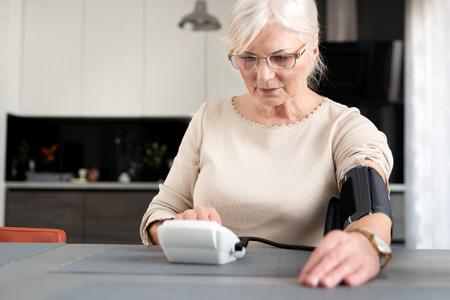 Senior adult woman measuring blood pressure at home Imagens