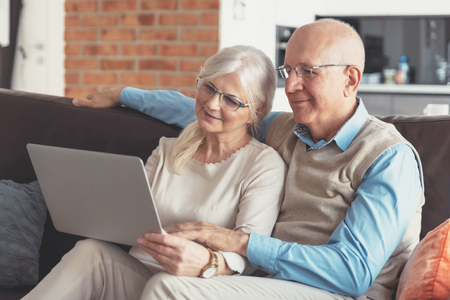 Senior couple browsing the internet together. Retirees using a laptop computer at home Imagens