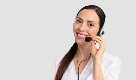 Consultor de call center en auriculares sobre fondo gris. Operador de la línea de ayuda con auriculares Foto de archivo