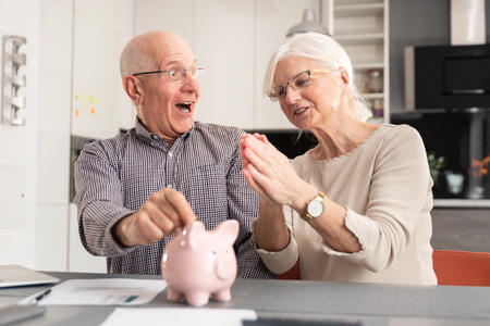Funny photo of mature couple putting coin into piggy bank at home. Savings, pension plan concept Zdjęcie Seryjne