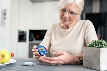 Senior woman with glucometer checking blood sugar level at home. Diabetes, health care concept Zdjęcie Seryjne