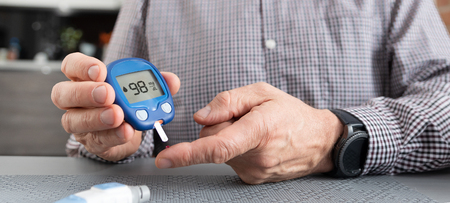 Senior man with glucometer checking blood sugar level at home. Diabetes, health care concept