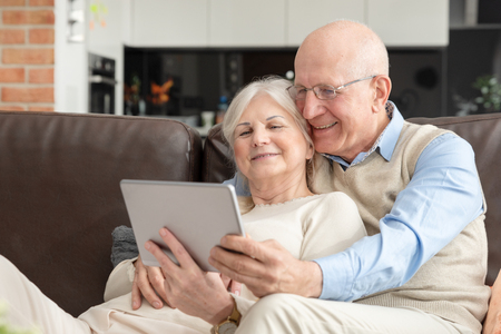 Senior couple with digital tablet at home. Grandparents using social media.