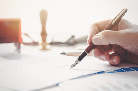 Il notaio firma il contratto legale. L'avvocato firma documento ufficiale Archivio Fotografico