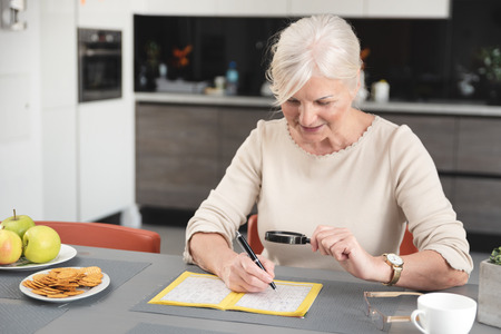 Senior woman enjoys solving a crossword puzzle at home