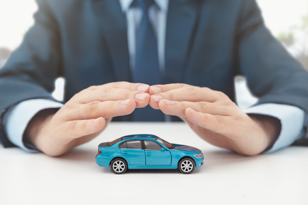 Car insurance, protection and safety concept. Insurance agent protects car with hands.