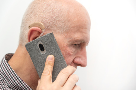 Hearing aid in the ear of aged old man. Senior using modern hearing aid while talking on the phone Zdjęcie Seryjne