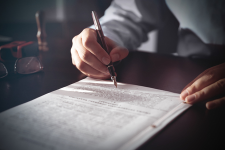 Notary signing a contract with fountain pen. Business man, attorney or advisor at work. Stock Photo