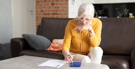 Senior woman with calculator and bills counting. Finances, savings concept. Web banner image background with copy space.