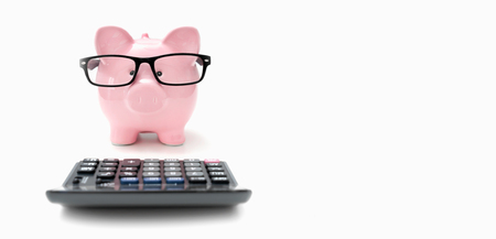 Piggy bank and calculator on white background. Savings and budget concept Zdjęcie Seryjne