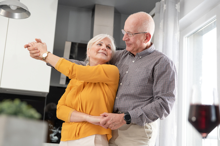 Senior couple dancing and smiling at home. Happy couple of pensioners