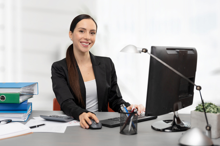 Business woman calculates tax. Happy accountant working in office Imagens