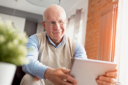 Elderly man using tablet PC. Senior sitting on sofa in living room