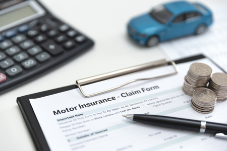 Motor or car insurance claim form with coin stack, calculator and car model. Zdjęcie Seryjne