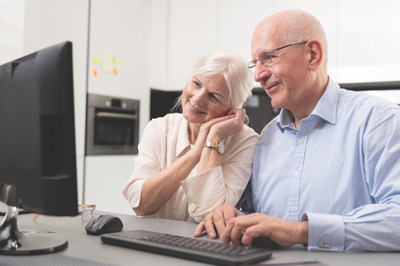 Happy elder couple enjoy together at computer. Seniors use a computer, they look at the pictures they have received. Zdjęcie Seryjne