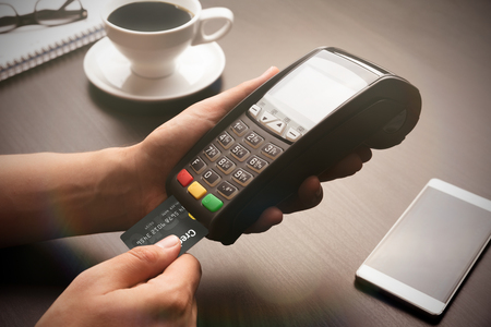 Man pays with the card in the restaurant. Payment terminal, POS device in hand Zdjęcie Seryjne