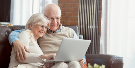 Senior couple browsing the internet together. Retirees using a laptop computer at home. Web banner image background with copy space