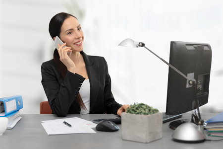 Business woman calculates tax. Accountant talking on the phone Zdjęcie Seryjne - 125165105