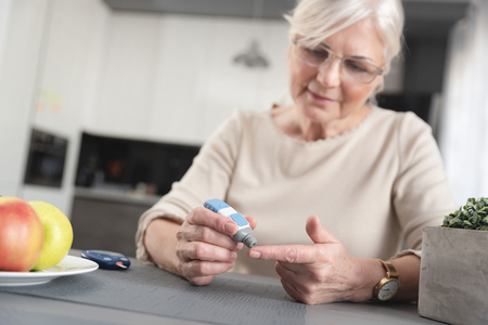 Senior woman checking her blood glucose level. Health care diabetes concept