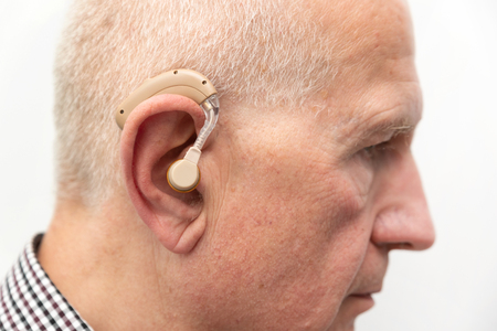 Hearing aid in the ear of aged old man. Senior using modern hearing aid