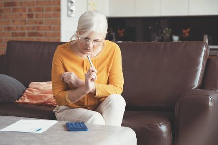 Senior woman with calculator and bills counting. Finances, savings concept