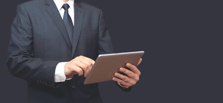 Man with digital tablet in hand. Unrecognizable person in suit, copy space wide image for banner.