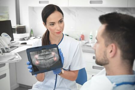 Female dentist showing teeth x-ray on digital tablet screen. Patient sitting on chair in professional dental clinic. Фото со стока