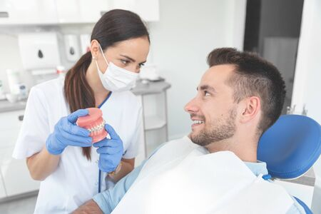 Female dentist holding jaw samples tooth with braces model. Professional dental clinic.