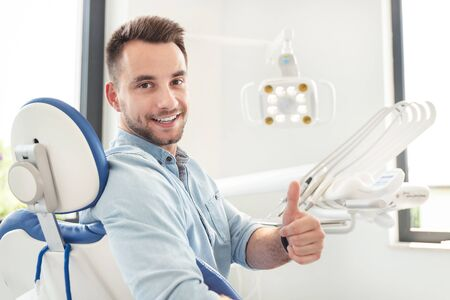 Handsome man showing thumbs up and smiling sitting at the dental chair. Professional dental clinic, healthy teeth concept. Фото со стока