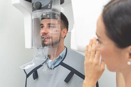 Paziente uomo bello in piedi nella macchina a raggi x. Radiografia panoramica presso lo studio dentistico professionale.
