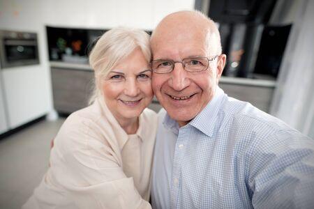 Cheerful senior couple taking selfie at home Фото со стока