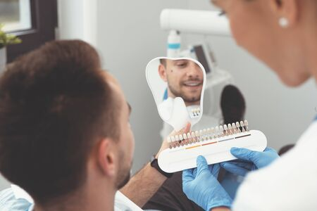 Handsome young man in stomatology clinic with female dentist. Healthy teeth whitening.