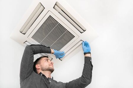 Handsome young technician repairing air conditioner. Installing air conditioning system.