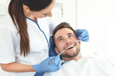 Man having teeth examined at dentists. Overview of dental caries prevention