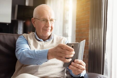 Senior man using a smartphone and smiling while sitting on couch at home. Фото со стока