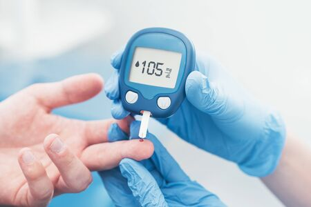 Doctor checking blood sugar level with glucometer. Treatment of diabetes concept. Stock Photo