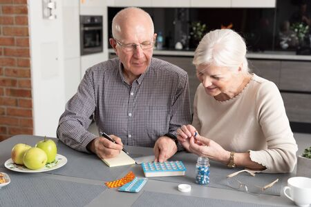 Senior couple talking about their medicines. Elderly people health care concept 写真素材