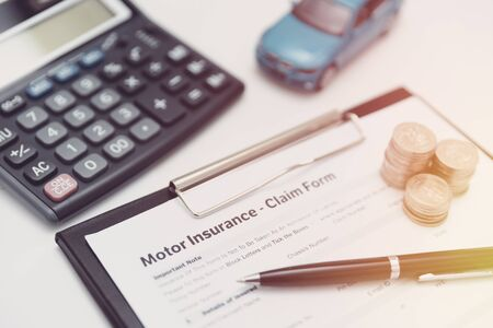 Motor or car insurance claim form with coin stack, calculator and car model. Фото со стока