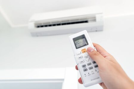 Adjusting temperature of air conditioner by remote. Air conditioning system Фото со стока