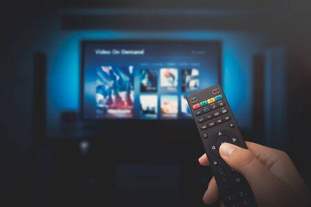 Pantalla de servicio VOD. Hombre viendo la televisión con el mando a distancia en la mano. Foto de archivo