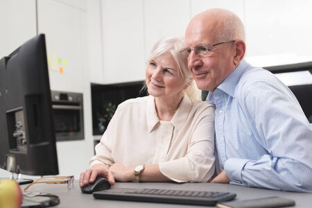 Happy elder couple enjoy together at computer. Seniors use a computer, they look at the pictures they have received. Фото со стока