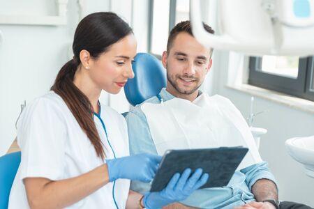 Female dentist with digital tablet. Modern treatment in professional dental clinic.