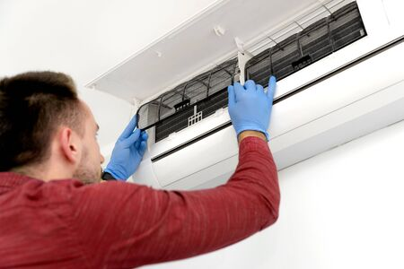 Technician repairing air conditioner appliance. Young man takes care of the cleanliness of the air-conditioning