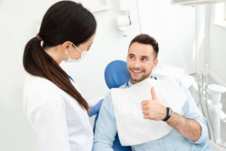 Young doctor dentist and patient showing thumb up. Healthy teeth concept.