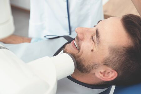 Dentist takes an x-ray picture of the tooth. Patient lying on chair. Dental care concept