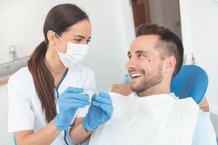 Dentist shows invisible braces aligner. Dental consultation in an orthodontic clinic