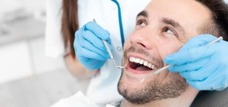 Young man at the dentist. Dental care, taking care of teeth. Picture with copy space for background. Stockfoto