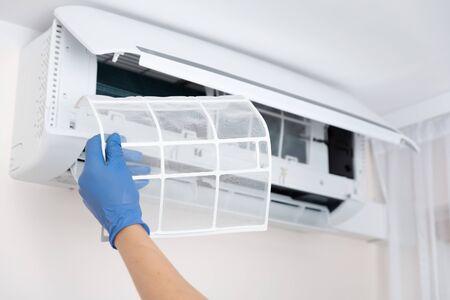 Técnico de limpieza de aire acondicionado. Mano sujetando el filtro de aire acondicionado Foto de archivo